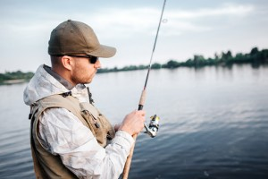 A picture of man in cap, sunglasses and vest standing in shallow and looking at fly rod. He is using non-inertial reel. Guy is concentrated